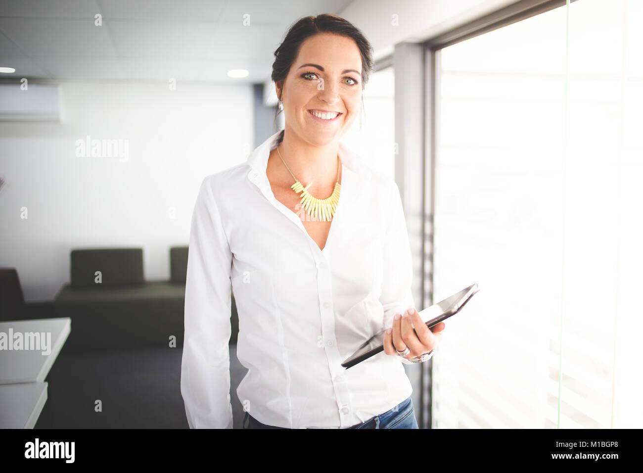 Schöne brünette Business woman Standing in einem Sitzungssaal arbeiten auf einem Tablet-PC Stockbild
