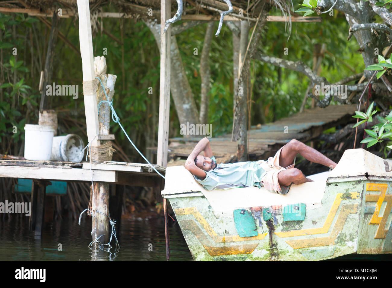 Madu Ganga, Balapitiya, Sri Lanka - Dezember 2015 - Ein Fischer seine Siesta auf einem Motorboot, Asien Stockfoto