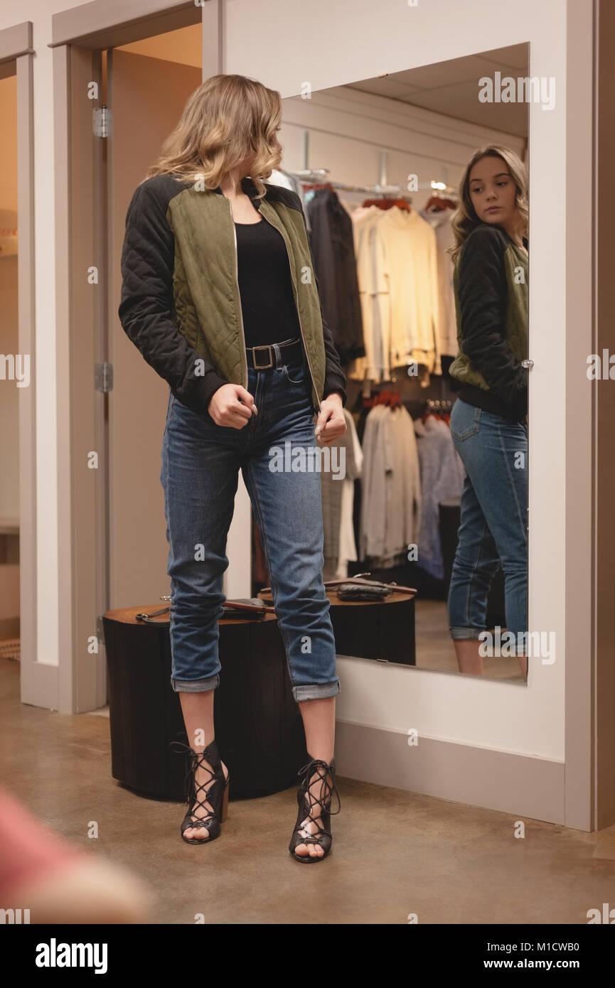 Schöne Frau prüfen Jacke vor dem Spiegel Stockbild