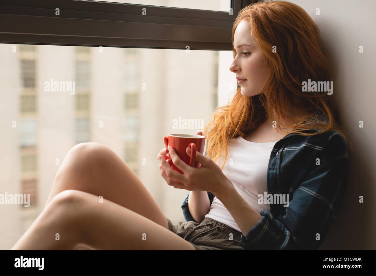 Frau mit Kaffee zu Hause Stockbild