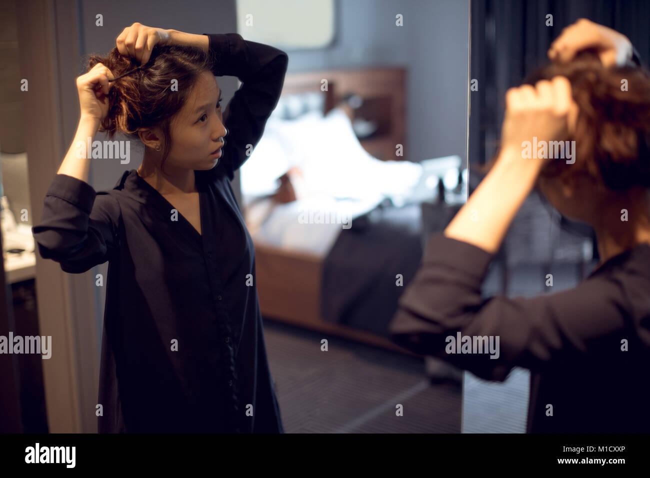 Frau fertig, vor dem Spiegel Stockbild