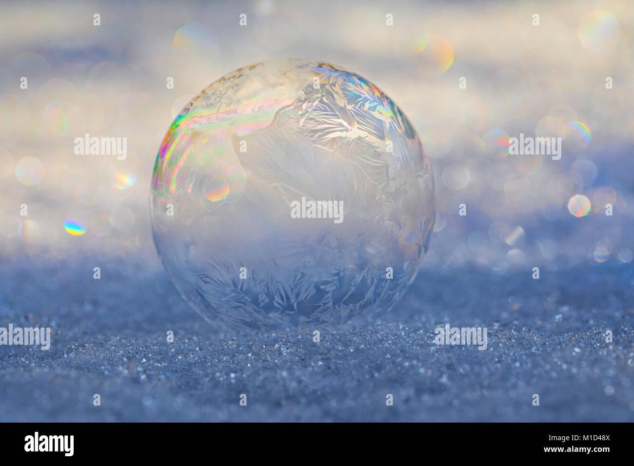 Frozen Bubble auf Schnee mit Eis die Bildung von Kristallen auf die Blase und brechende Licht erzeugen Prisma Muster Stockfoto