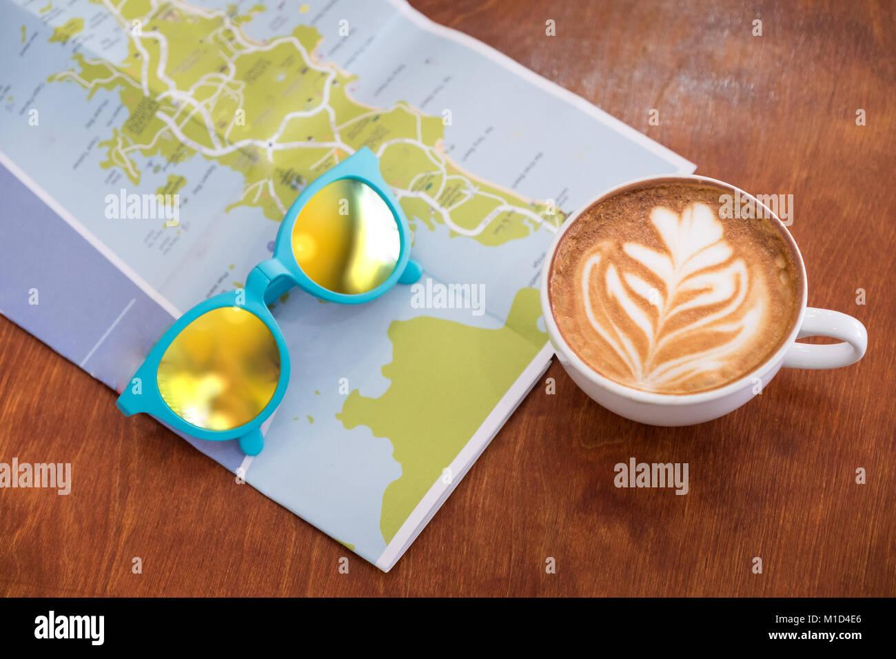 Weiß Kaffeetasse mit Latte Art mit Karte und Sonnenbrille auf braunem Holz Tisch, Freizeit Aktivität. Stockbild