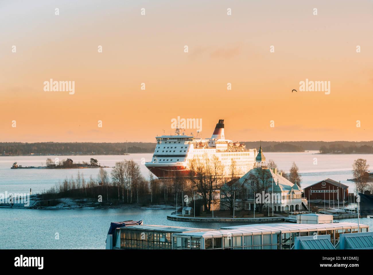 Helsinki, Finnland. Ansicht der modernen Fähre Fähre Segeln in der Nähe von Blekholmen Valkosaari Insel auf dem Hintergrund der Sonnenuntergang Sonnenaufgang Himmel. Stockfoto
