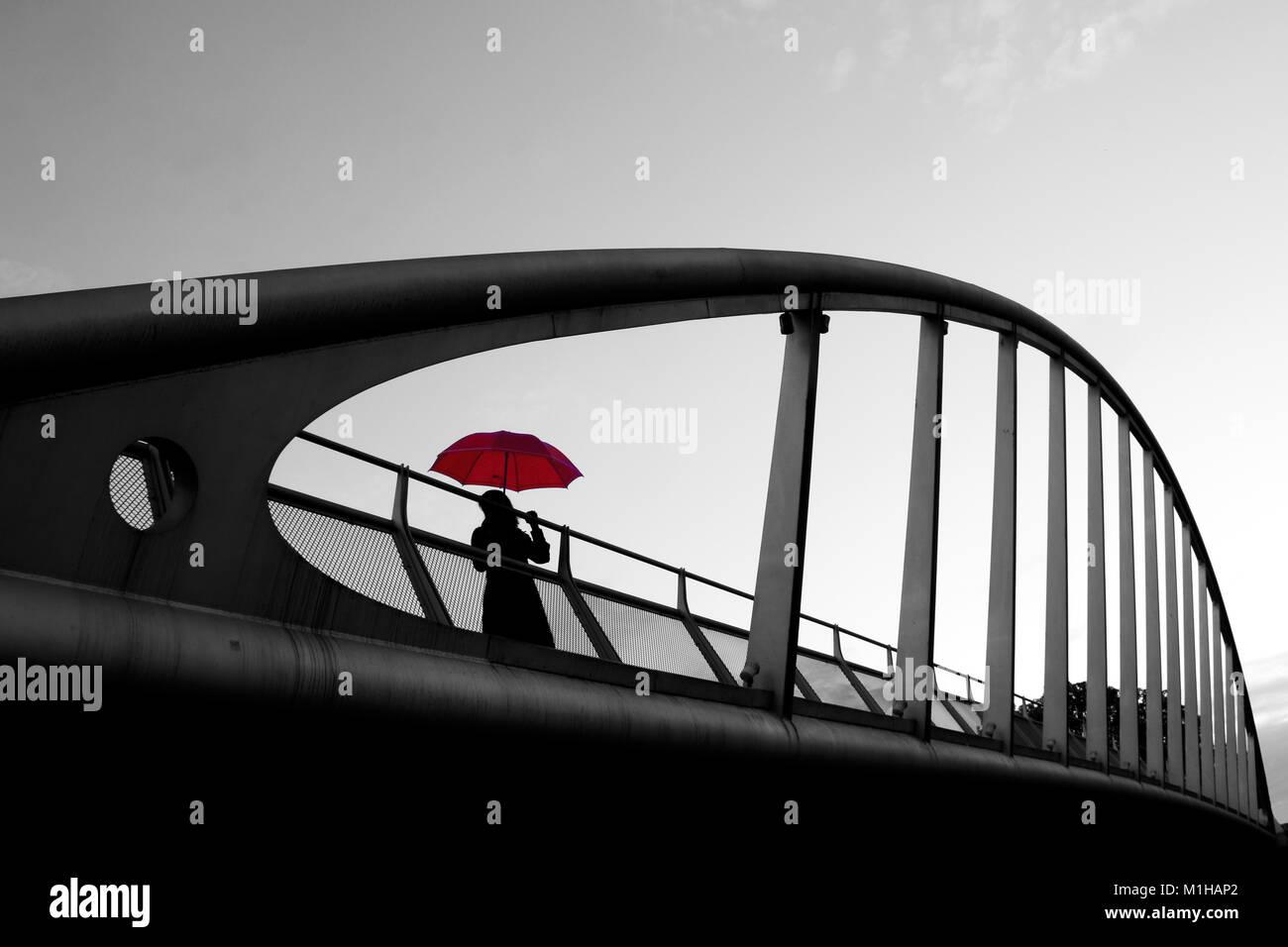 Ein künstliches Bild einer Frau auf einer Brücke mit einem roten Regenschirm während der regnerischen Tag. Der Schirm Stockfoto