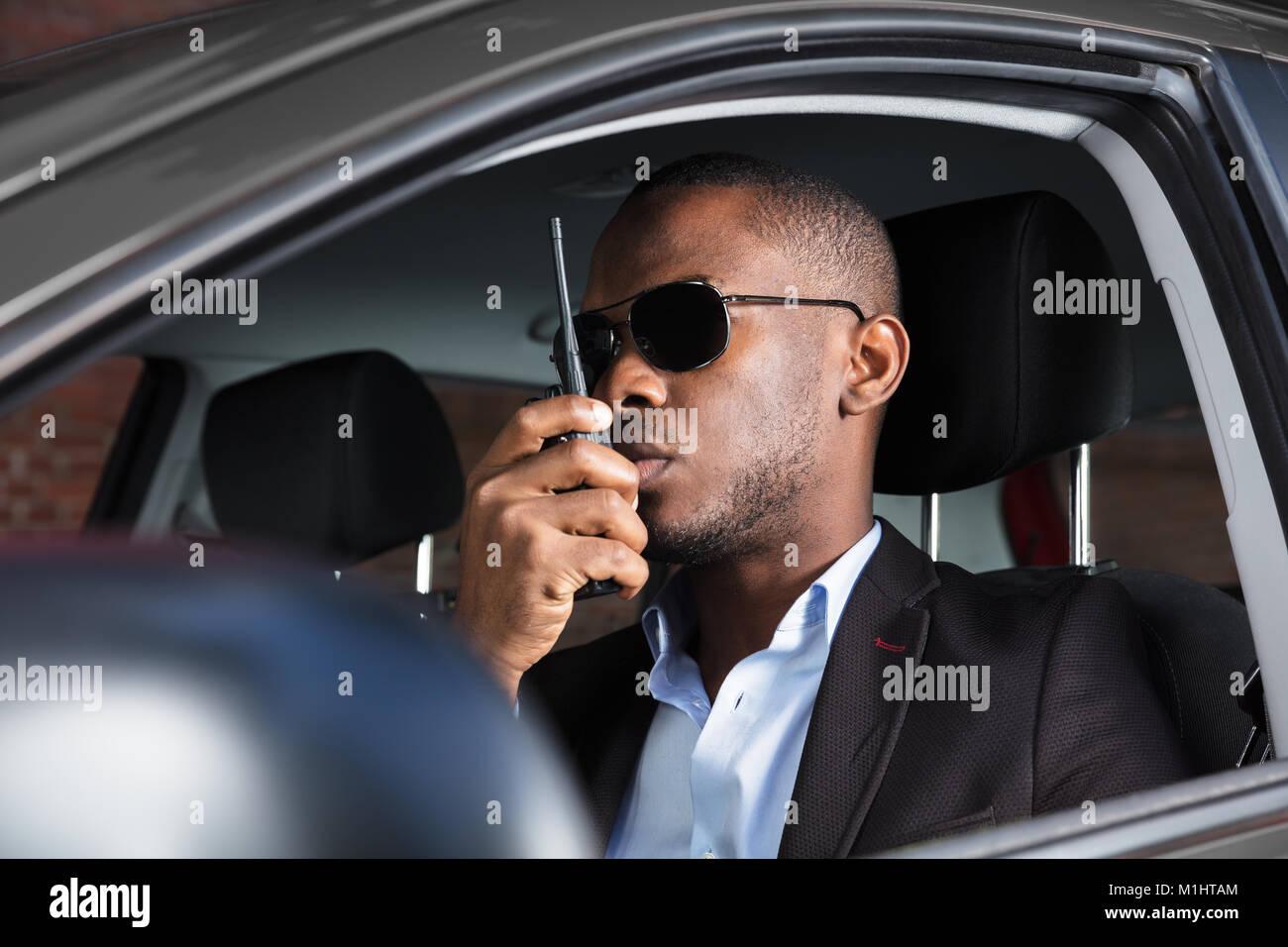 Überwachung Mann mit Sonnenbrille Sitzen im Auto mit Walkie Talkie Stockbild