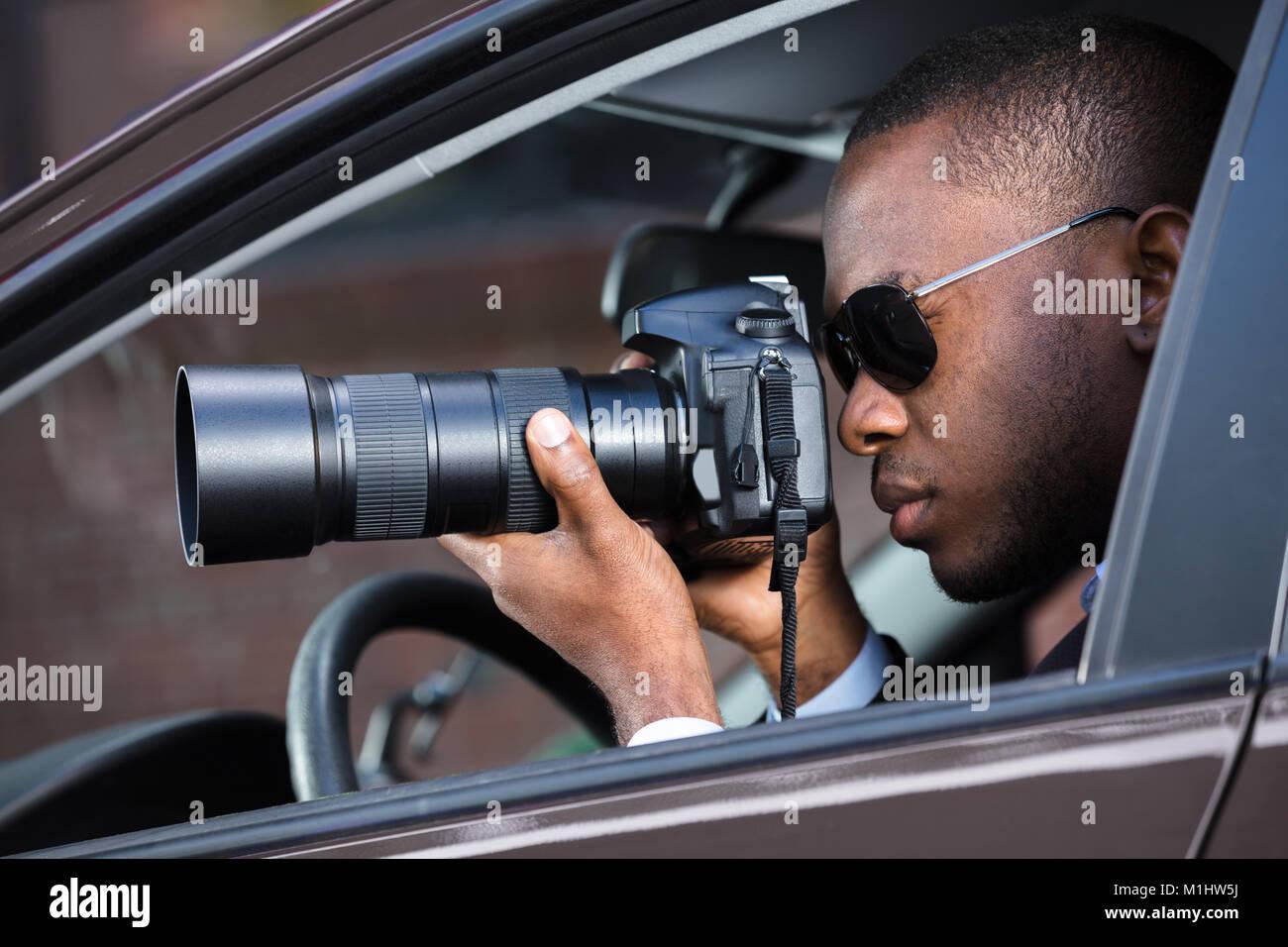 Privatdetektiv Sitzen im Auto Fotografieren mit SLR-Kamera Stockbild