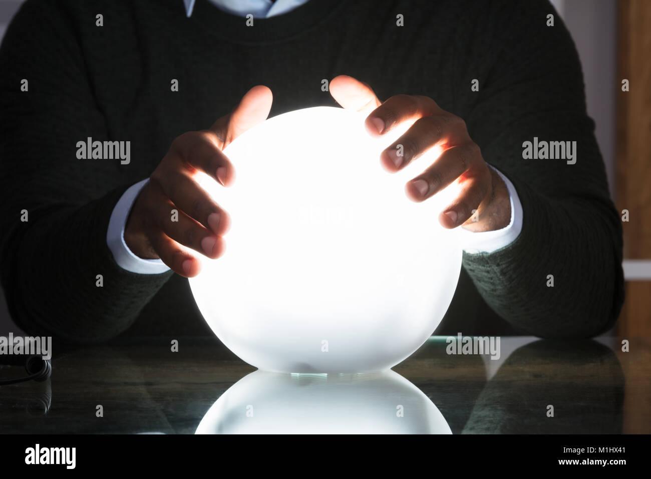 Nahaufnahme der Geschäftsmann Hände auf Crystal Ball auf dem Schreibtisch im Büro Stockbild