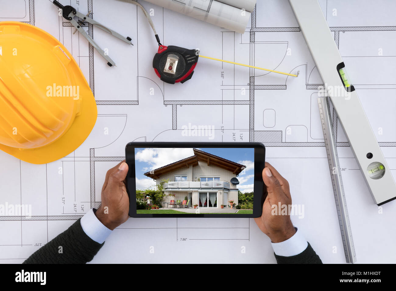 Männliche Architekt suchen Bei Digital Tablet über Blueprint Stockbild