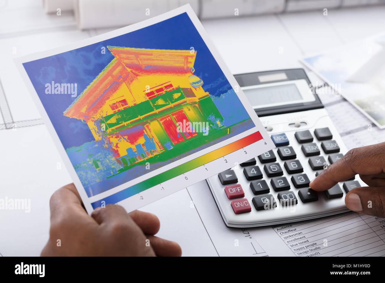 Nahaufnahme der Person Hand Berechnung von Temperatur mit dem Rechner auf dem Schreibtisch Stockbild