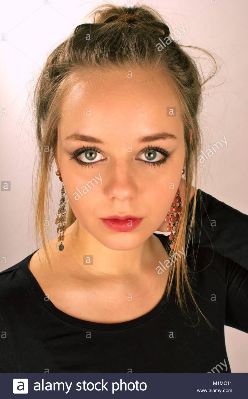 Teenager Maedchen mit blonder Hochsteckfrisur, auffaelligen Ohrringen und grossen Augen schaut mit leichtem Schmollmund Stockbild