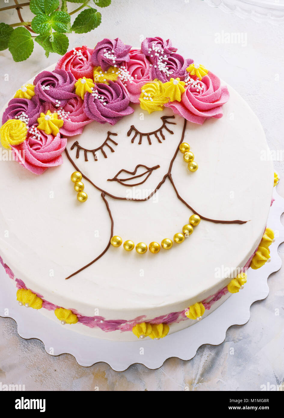 Festliche Kuchen mit Sahne Blumen und ein Mädchen Gesicht auf einen hellen Hintergrund Stockbild