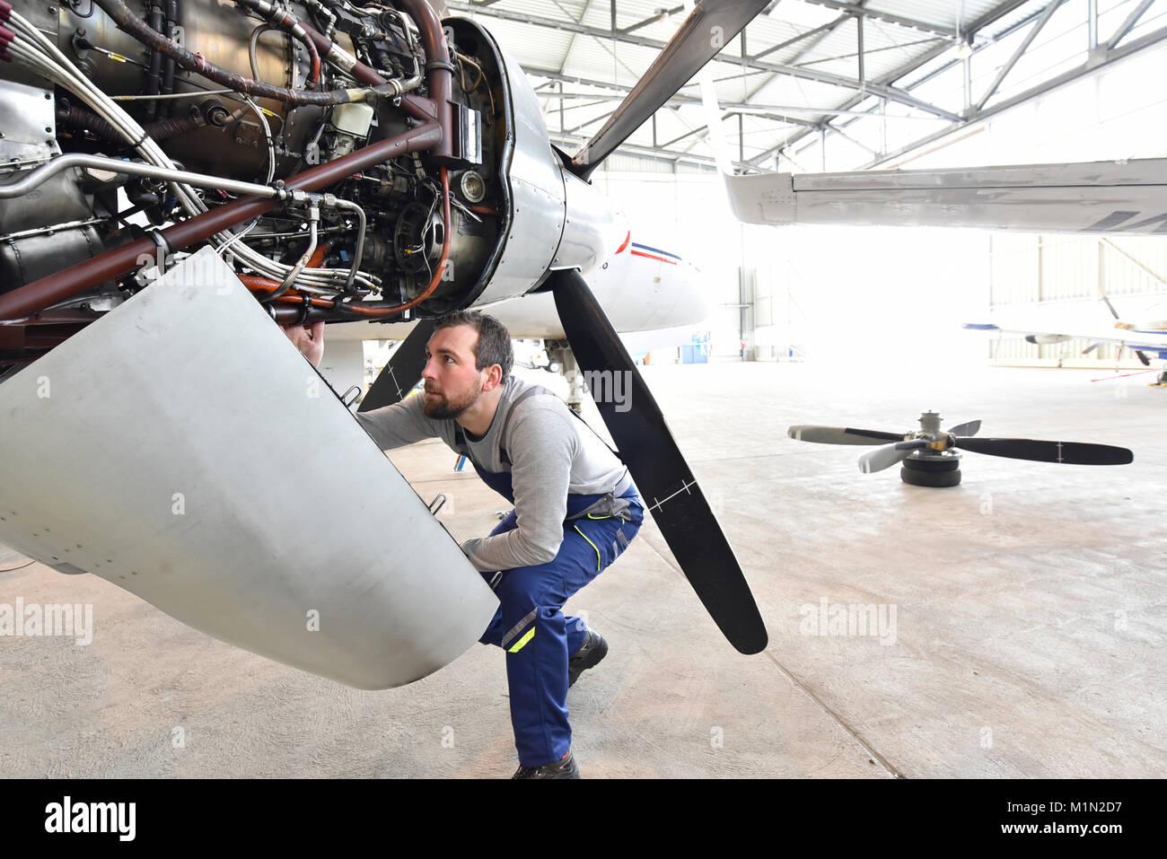 Fluggerätmechaniker Reparaturen Triebwerk in einem Flughafen Hangar Stockfoto