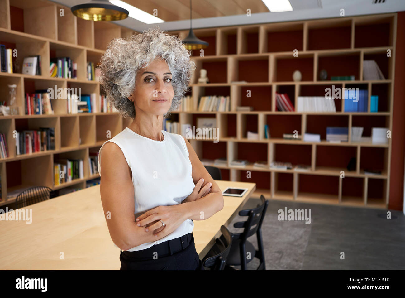 Senior Geschäftsfrau im Sitzungssaal zu Kamera suchen Stockbild
