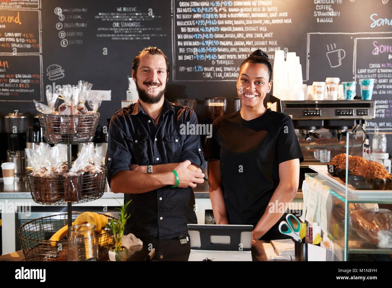 Männliche und weibliche Baristas hinter Zähler in Coffee Shop Stockfoto