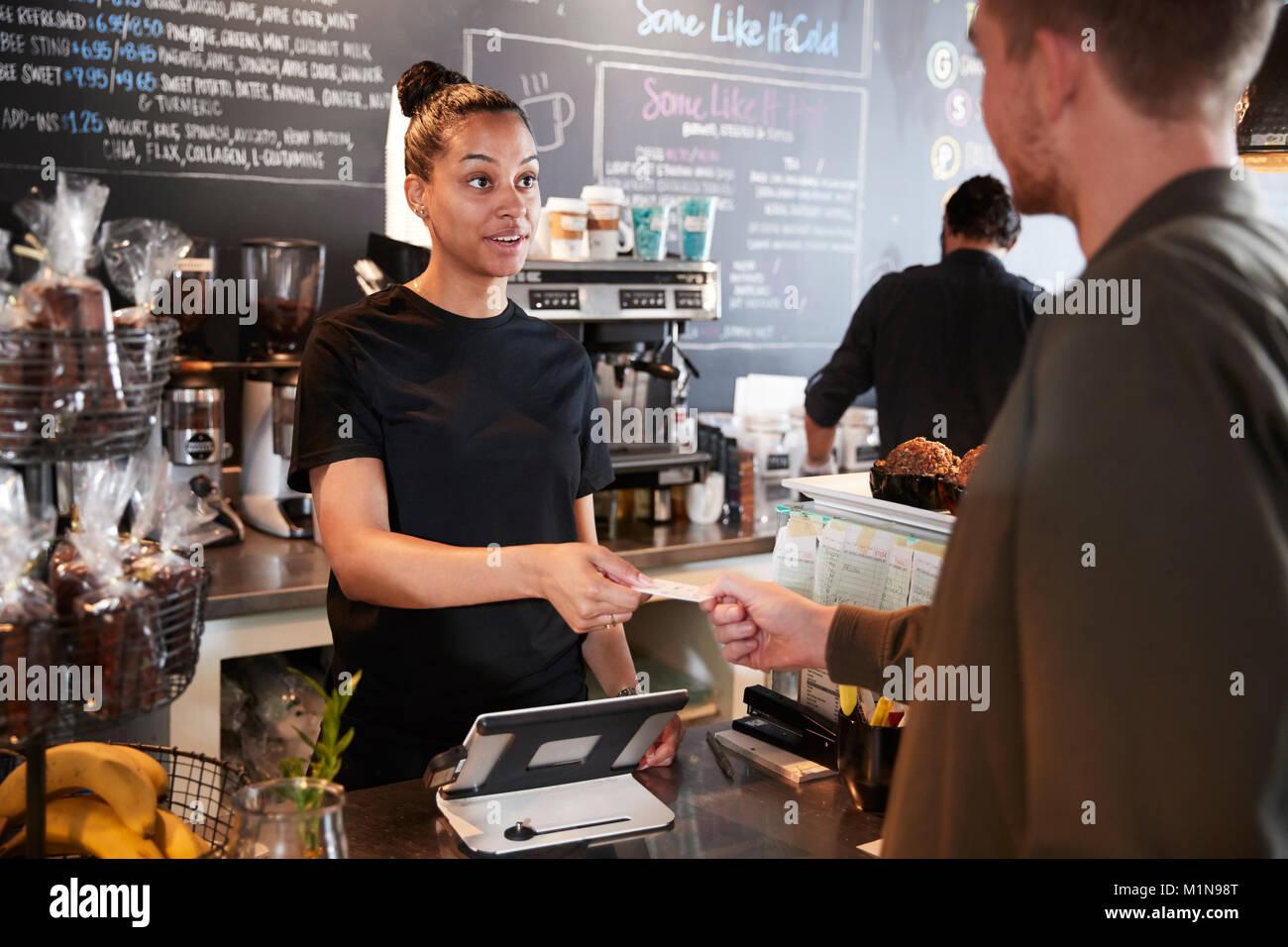 Kunden zahlen im Coffee Shop mit Kreditkarte Stockbild