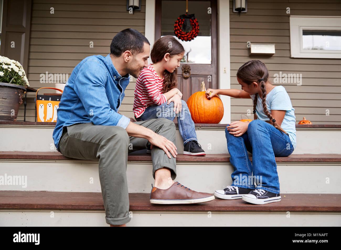 Vater und Tochter Zeichnung Gesicht auf Halloween Kürbis Stockbild