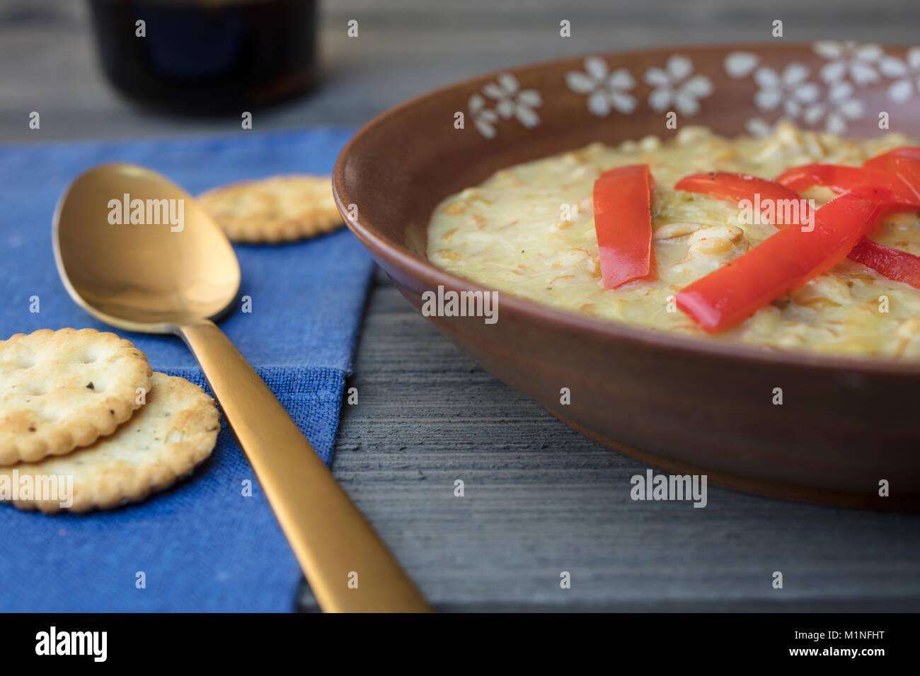 Korn Farro Suppe mit Paprika und Service in einem braunen Keramik Schüssel mit einem blau serviette und Gold Stockbild