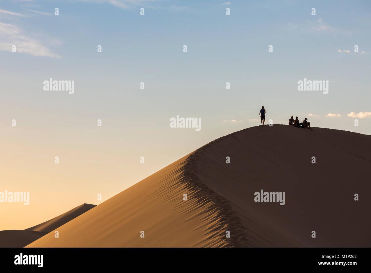 Menschen in Silhouette auf Khongor Sanddünen in der Wüste Gobi Gurvan Saikhan Nationalpark, Sevrei Bezirk, Stockbild
