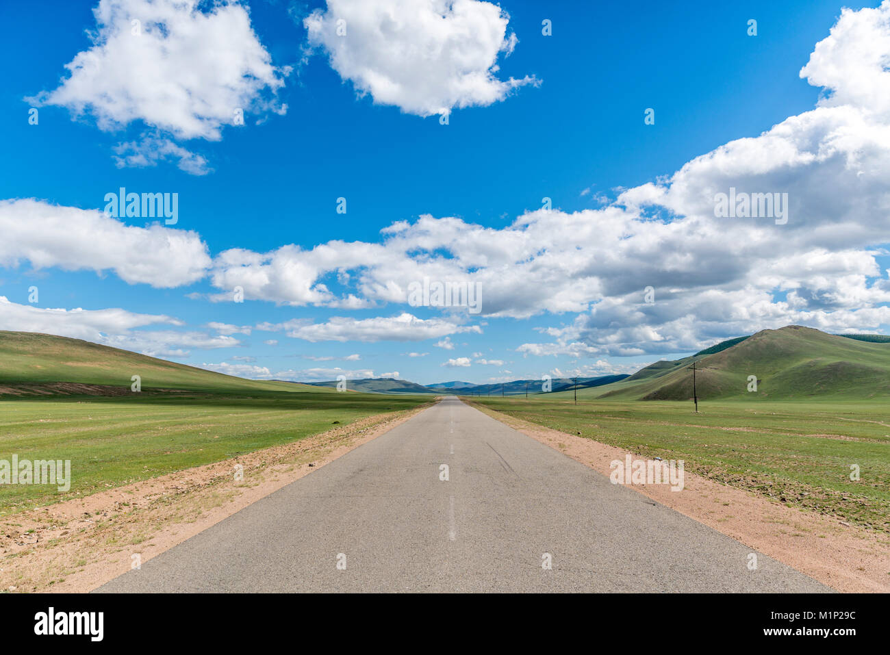 Gerade Straße in der mongolischen Steppe und Wolken im Himmel,Hangay Provinz, Mongolei, Zentralasien, Asien Stockbild