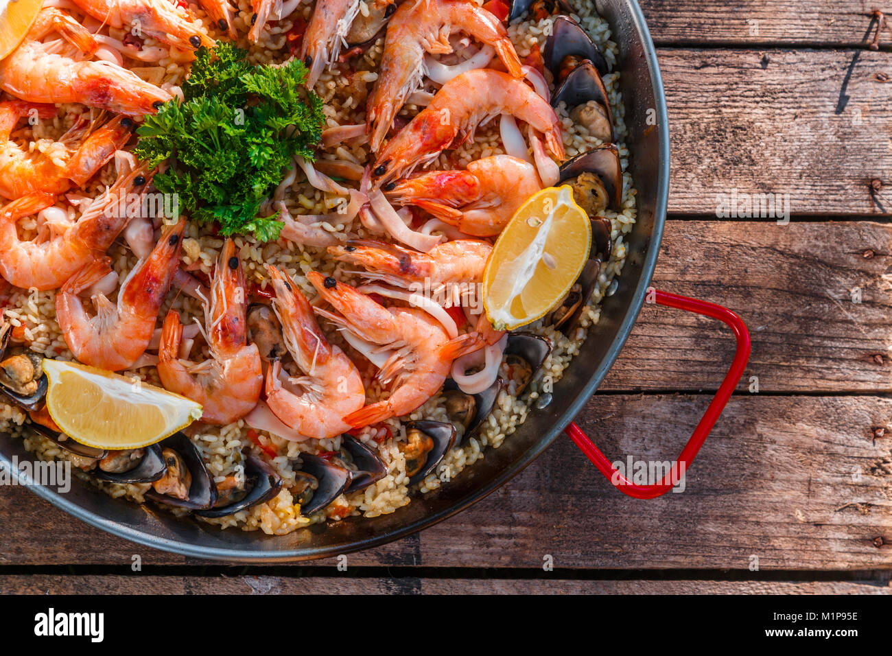 Traditionellen Meeresfrüchte Paella in der Pfanne anbraten, auf einem alten Holztisch, Ansicht von oben Stockbild