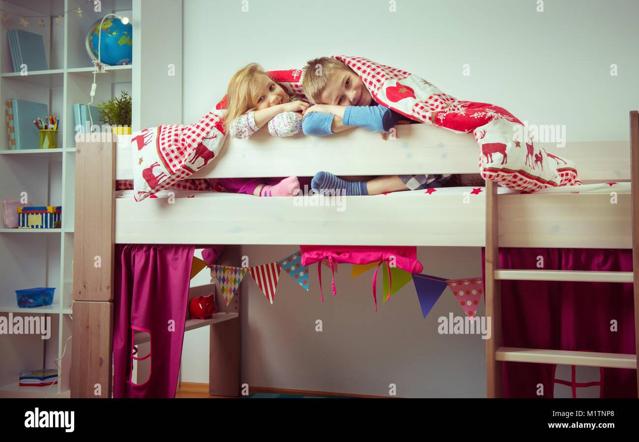 Zwei Glückliche Geschwister Kinder Spaß Im Etagenbett Unter Vertrag  Stockbild