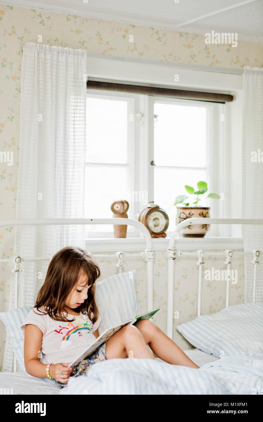 Mädchen im Bett lesen Stockbild