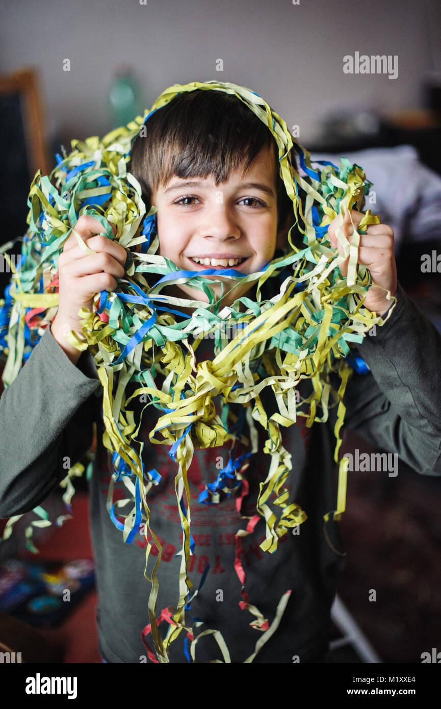 Kind mit Luftschlangen um den Hals und Kopf für die Faschingsfeier in seinem Haus Stockbild
