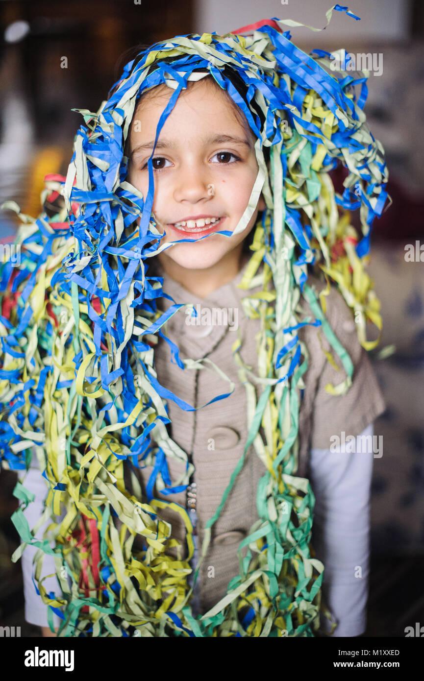 Kind kleines Mädchen mit Luftschlangen um den Hals und Kopf für die Faschingsfeier in seinem Haus Stockfoto