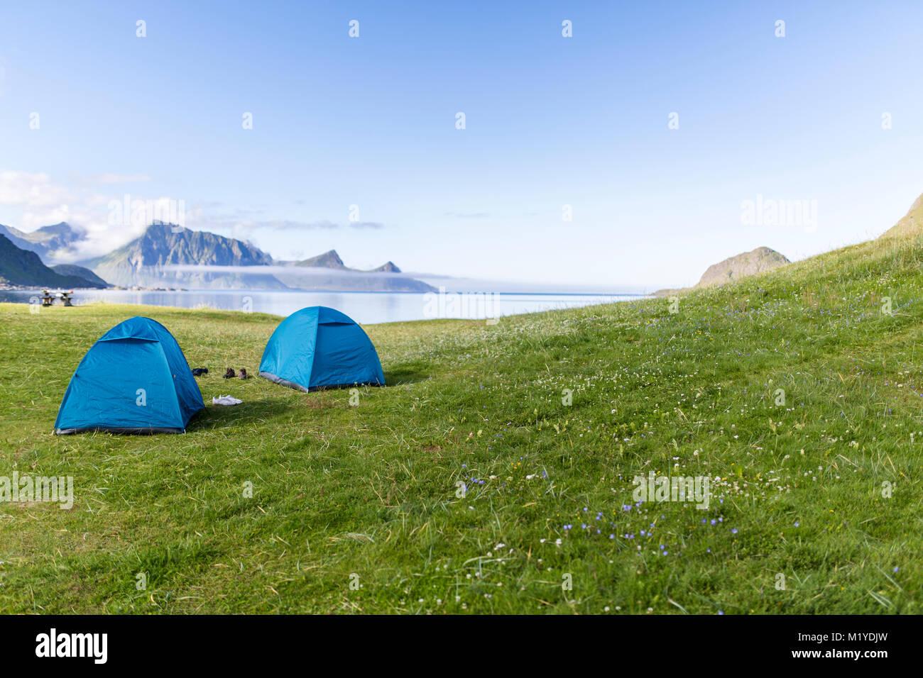 Zwei Zelte in das grüne Gras vor dem Meer. Haukland Strand, Lofoten, Norwegen. Stockfoto