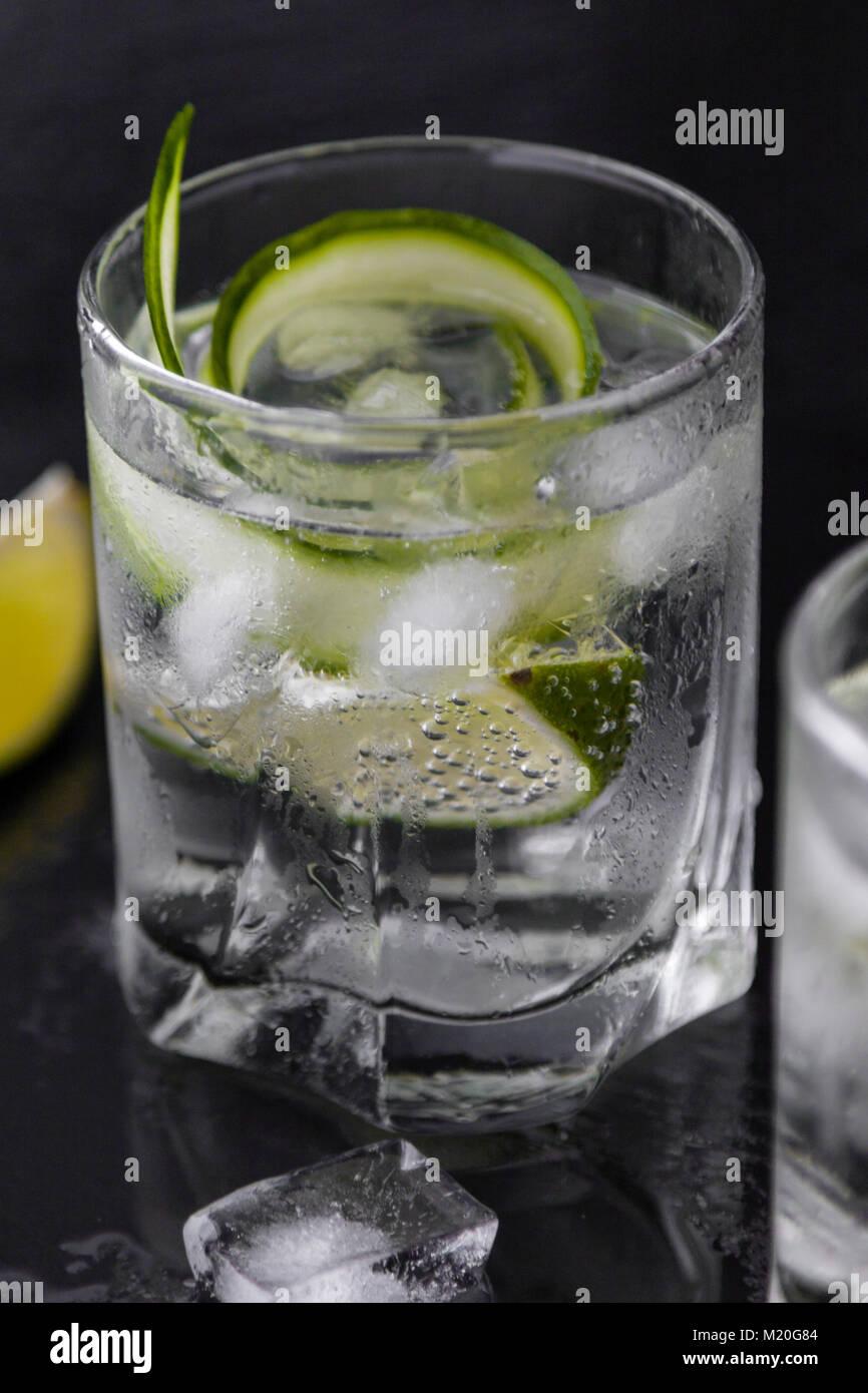 Gin Tonic mit Gurke, Kalk und Eis im Glas Stockbild