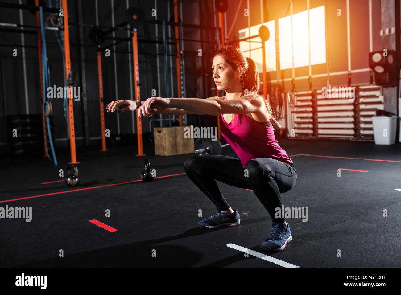 Athletic girl hat Kniebeuge Übungen im Fitnessstudio Stockbild
