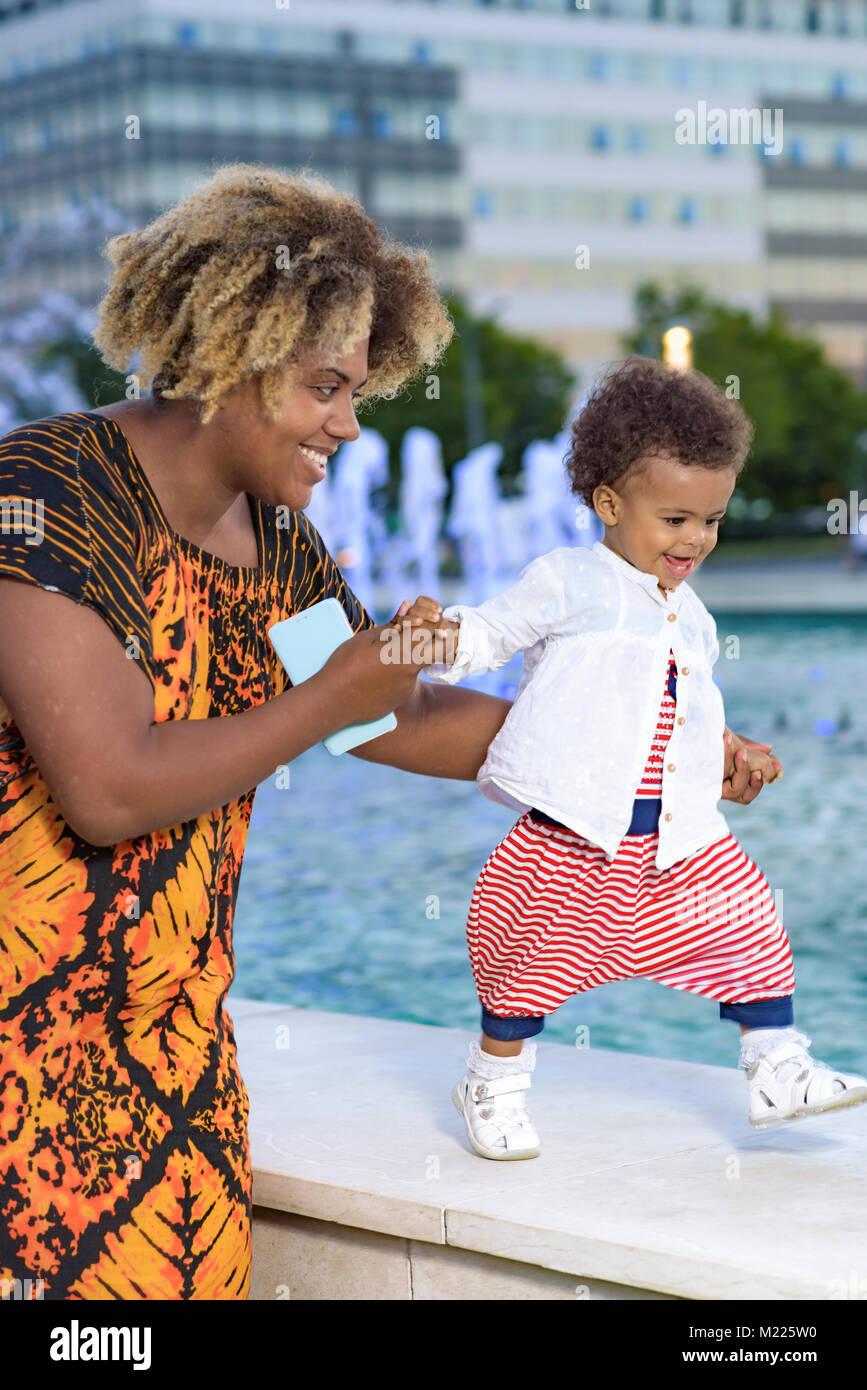 Die ersten Schritte ihres Babys Tochter Stockbild