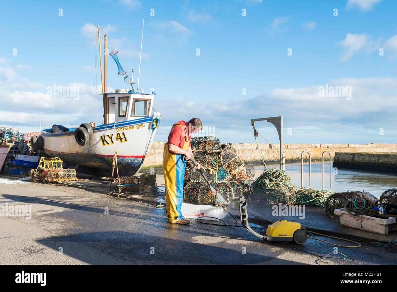 Fischer Reinigung Hummer Töpfe und kleinen potter Fischerboot in St Andrews Harbour, St Andrews, Schottland, Stockbild
