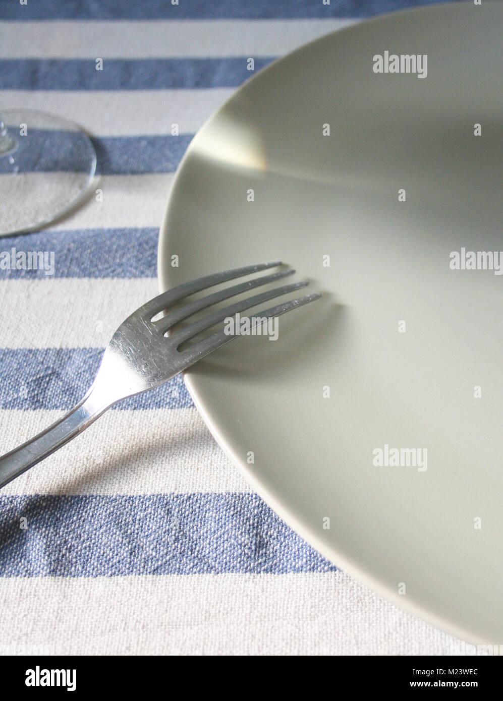 Gabel ruht auf einem leeren weißen Platte auf eine blau-weiße Tischdecke und Glas Stockbild