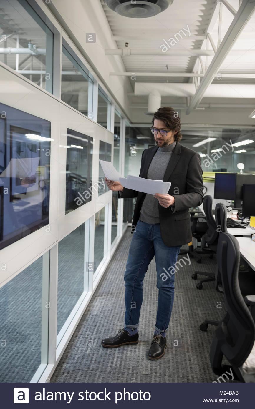Geschäftsmann Schreibarbeit überprüfung auf Bildschirmen im Büro Stockbild