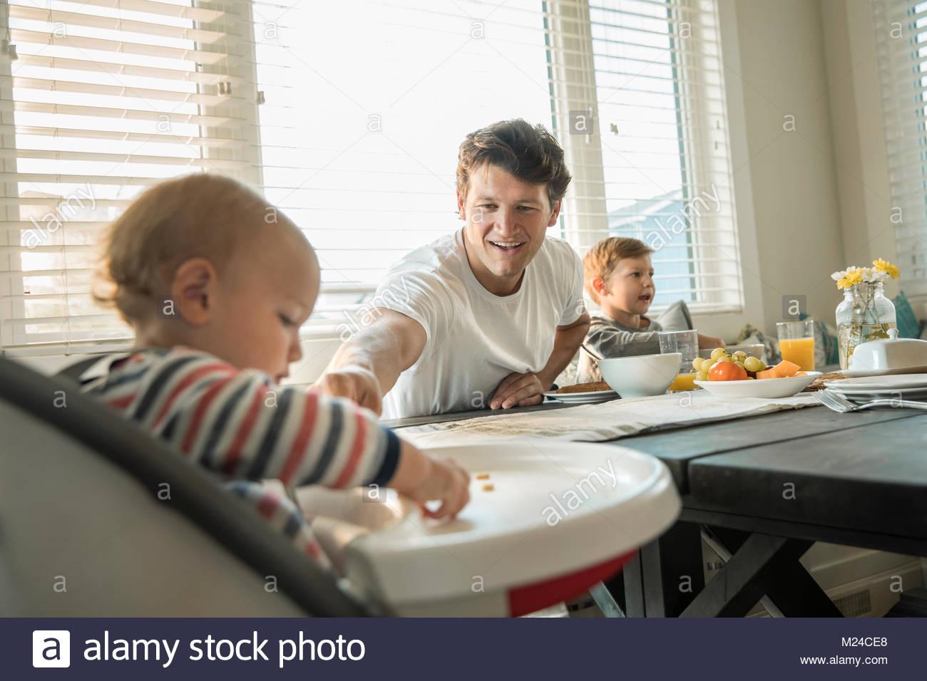 Vater Fütterung Baby Sohn im Hochstuhl Stockbild