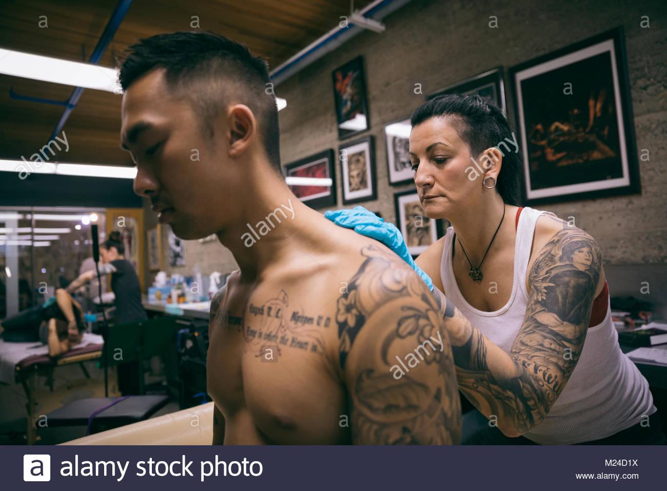 Tattoo Künstler Rücken tätowieren von Client in tattoo studio Stockbild