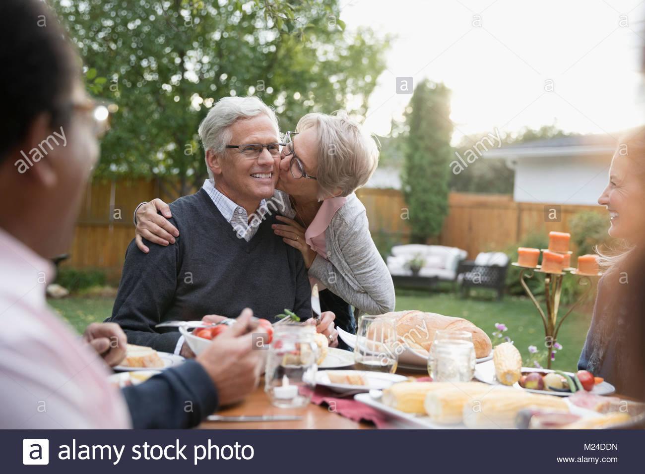 Liebevolle ältere Frau Mann Küssen auf die Wange an Garden Party Mittagessen Terrasse Tisch Stockbild