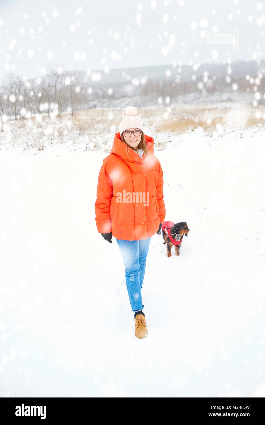 Volle Länge geschossen von einer glücklichen Frau zu Fuß ihrer kleinen Hund im Freien im Winter. Stockbild