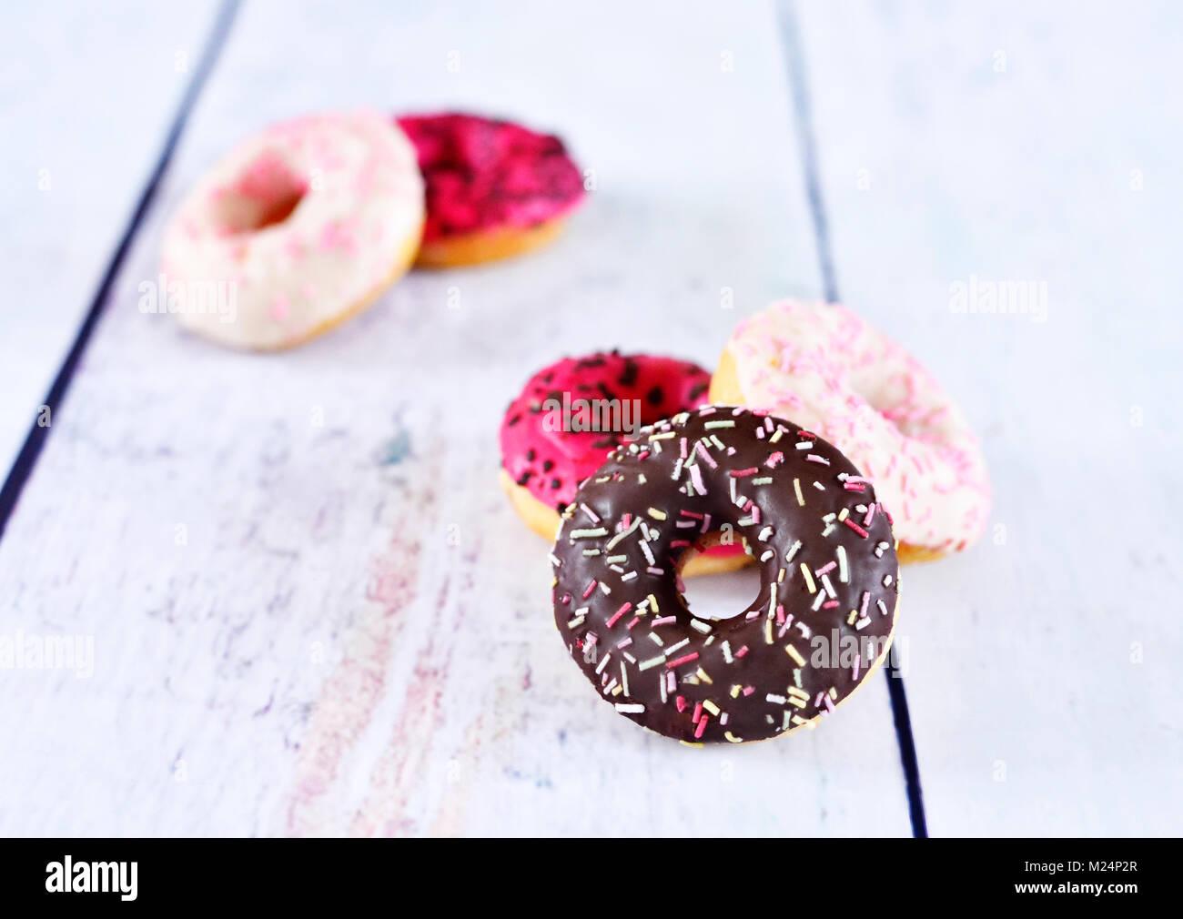 Delicious Doughnuts mit Glasur oder Vereisung und Streuseln. Variation von frischen Donuts auf einem weißen Stockbild