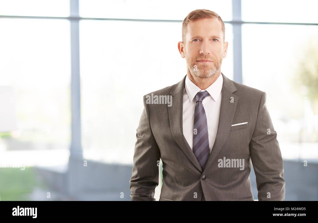 Lächelnd executive Financial Director Geschäftsmann stand im Büro. Stockbild