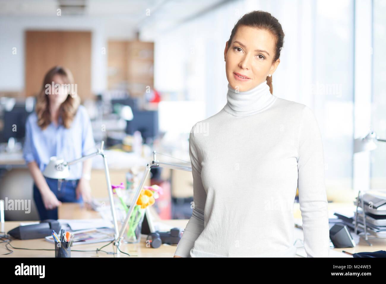 Smiling brunette Geschäftsfrau rollkragen pullover tragen, während Sie im Büro stehen und von der Stockbild