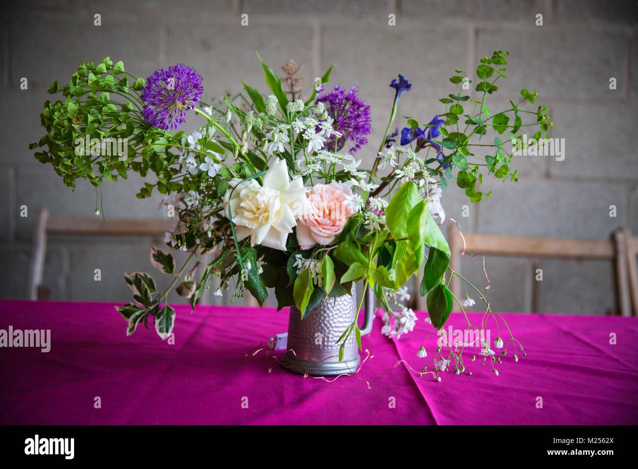 Hochzeitstisch Blumenschmuck auf rosa Tischdecke Stockfoto