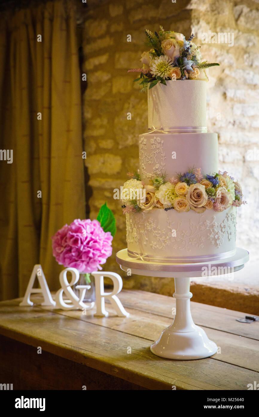 Frische Blumen auf drei abgestufte Hochzeitstorte auf Kuchen stand Stockbild