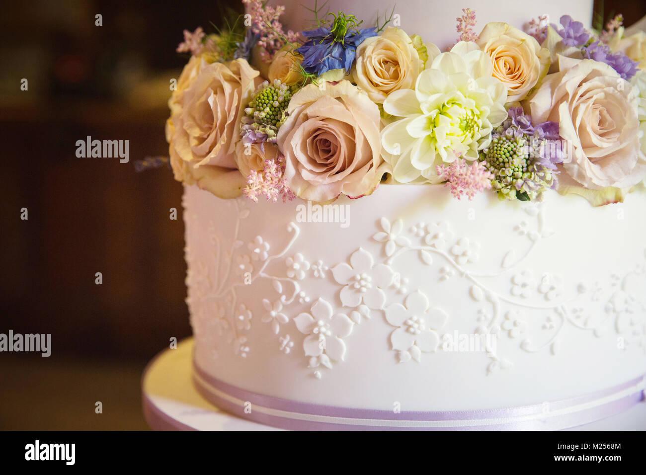 Frische Blumen auf der Stufe der Hochzeitstorte, Nahaufnahme Stockbild