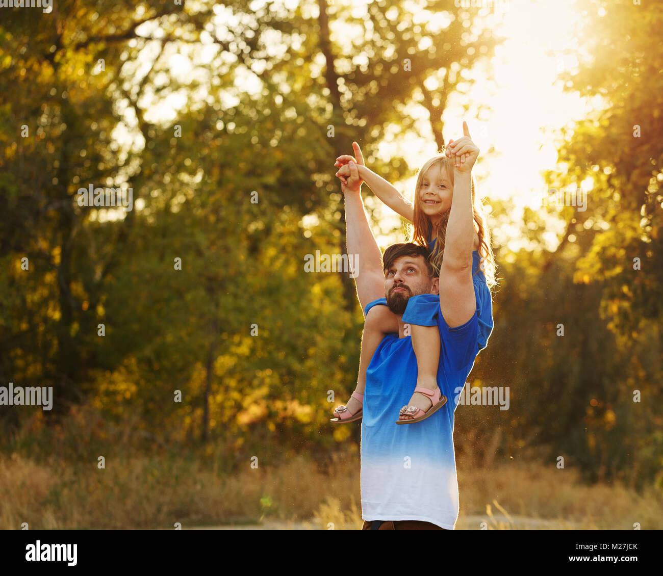 Zeit mit der Familie. Der Vater hält die Tochter auf den Schultern von Piggyback. Er unterstützt das kleine Stockbild