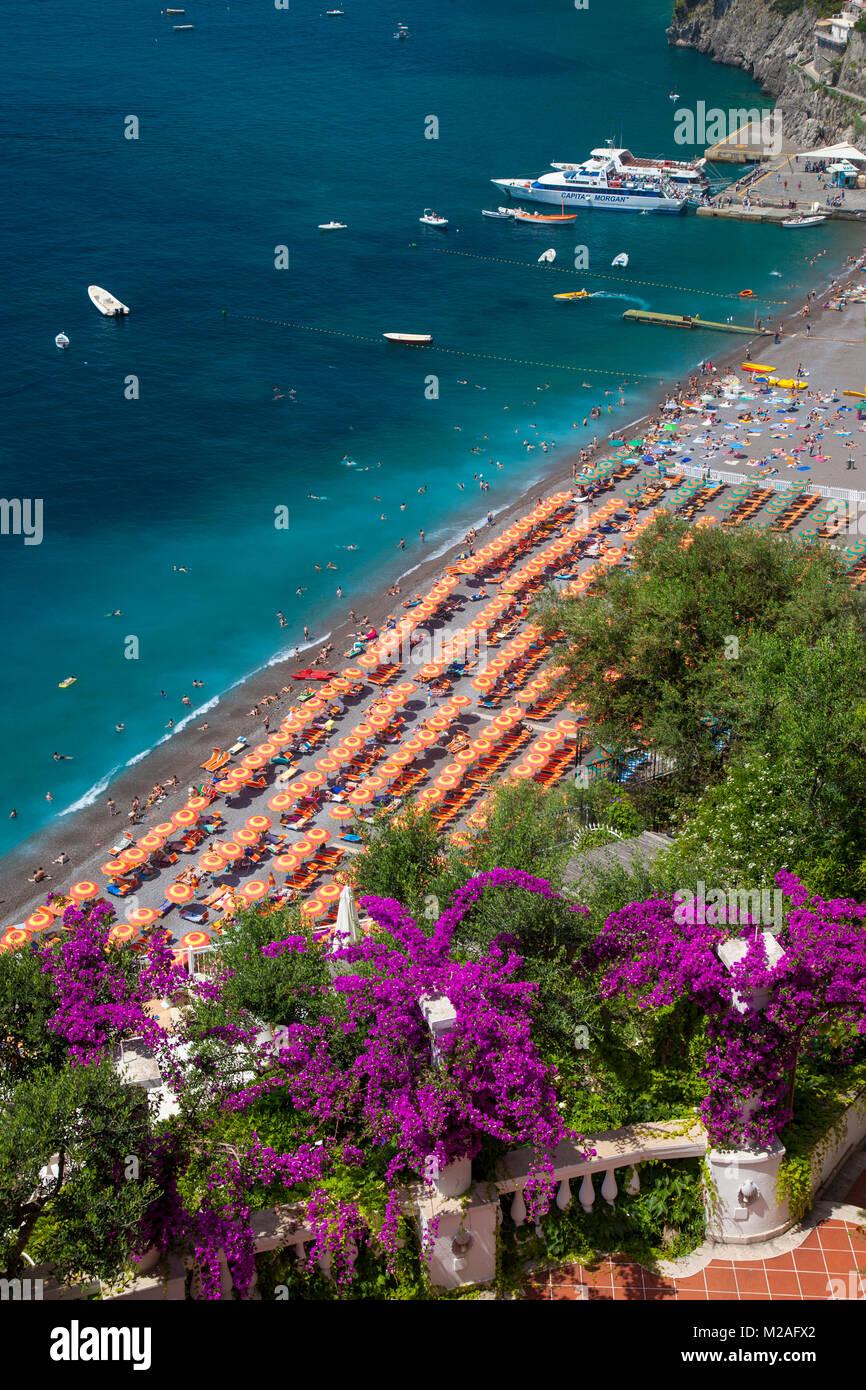 Resort Hotel blicken Sie auf den orangefarbenen Sonnenschirme am Strand entlang in Positano, Kampanien, Italien Stockbild
