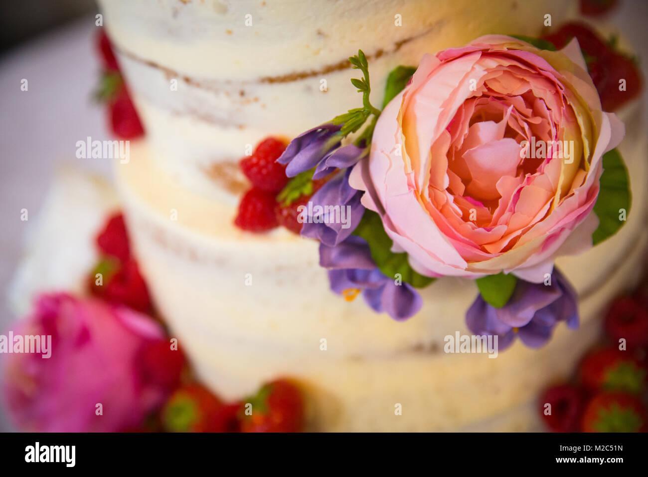 Frische Blumen und Obst auf mehrstufige Feier Kuchen, close-up Stockbild