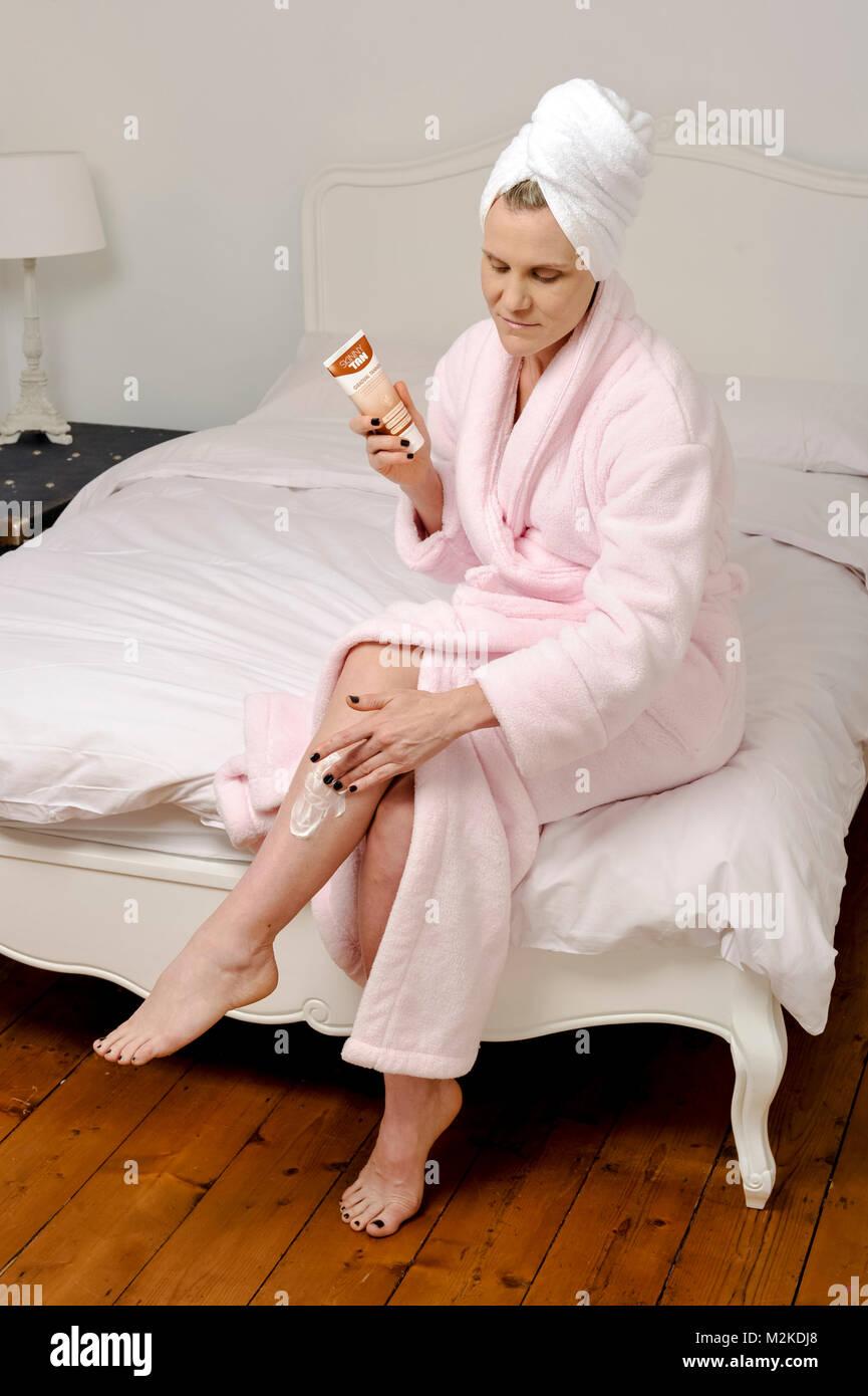 Frau in ihrem Schlafzimmer mit Schönheitsbehandlungen, bevor sie schläft. Stockbild